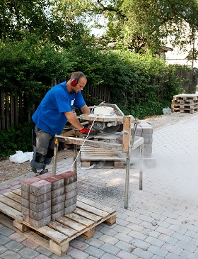 guy cutting concrete blocks in backyard